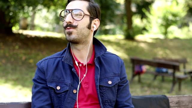 junger mann mit mustaches musik hören - uncool stock-videos und b-roll-filmmaterial