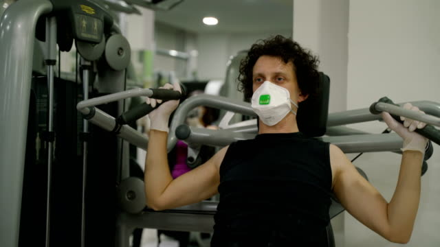 young  guy working out in gym during covid-19 pandemic,wearing face mask and rubber gloves,protection and virus spread and transfer prevention,social distancing activity rules and guidelines - gym stock videos & royalty-free footage