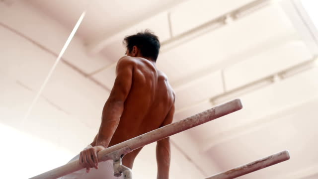 Young gymnast in balanced position on parallel bars