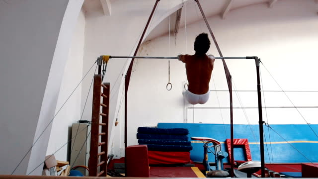 young gymnast performing routine on horizontal bar - horizontal bar stock videos and b-roll footage