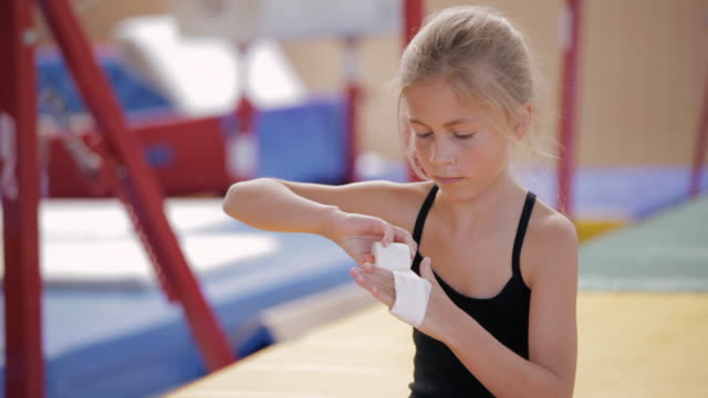 PAN Young gymnast wrapping tape around hand / Vancouver, British Columbia, Canada