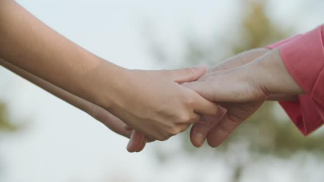 junge hände unterstützen alte hände - hände verschränken stock-videos und b-roll-filmmaterial