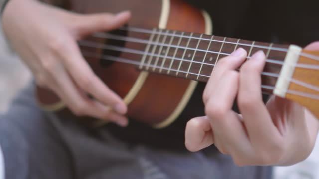 vídeos de stock, filmes e b-roll de ecu mãos jovens jogando ukulele - ukulele