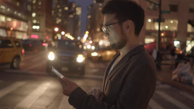 young handsome asian man using digital tablet computer device in the city at night. urban people lifestyle portrait - goatee stock videos & royalty-free footage
