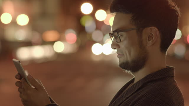 young handsome asian man using digital tablet computer device in the city at night. urban people lifestyle portrait