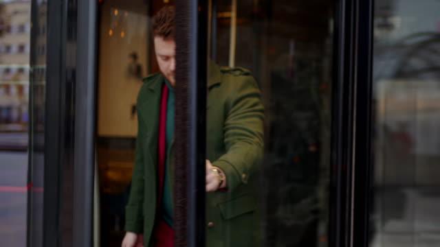 junger hübscher geschäftsmann verlässt das hotel - europäischer abstammung stock-videos und b-roll-filmmaterial