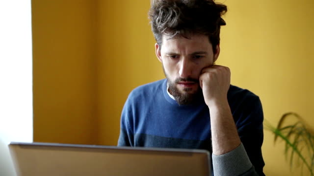 Young handsome hipster bearded man working in office on laptop
