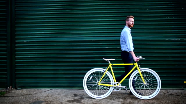 young handsome male walking with yellow retro bike - side view stock videos & royalty-free footage