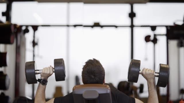 vídeos de stock, filmes e b-roll de homem considerável novo que faz exercícios na ginástica. seqüência do movimento lento do homem na ginástica que exercita com pesos. - musculação
