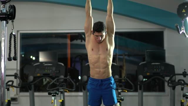 stockvideo's en b-roll-footage met jonge knappe man doen oefeningen in de sportschool - oefeningen met lichaamsgewicht
