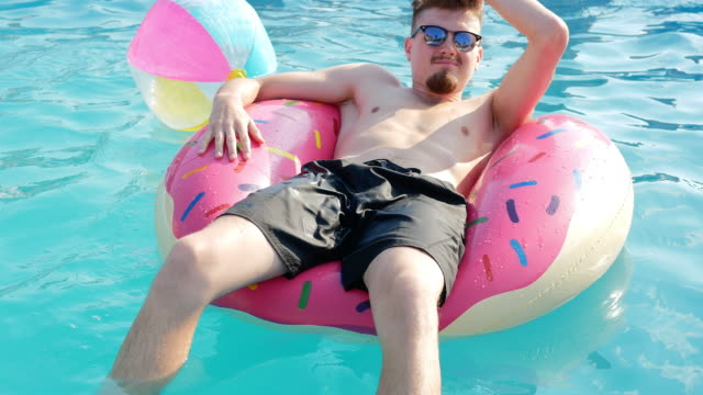 Young handsome man enjoys summer in swimming pool