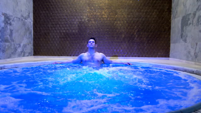 young handsome man relaxing in hot tub - whirlpool stock videos & royalty-free footage