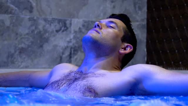 vídeos de stock e filmes b-roll de young handsome man relaxing in hot tub - fonte termal