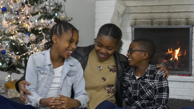 Young happy African American siblings laughing on Christmas Morning