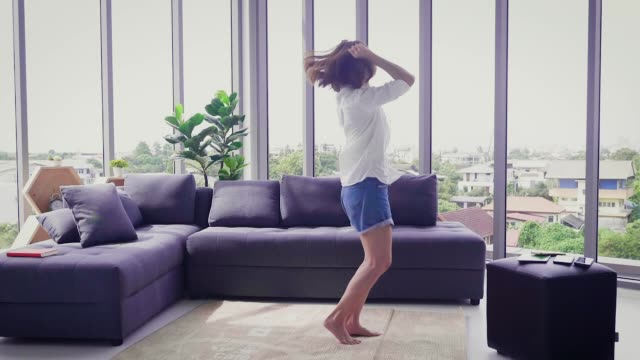 vídeos de stock e filmes b-roll de young happy asian woman having fun dancing in living room at home - full length