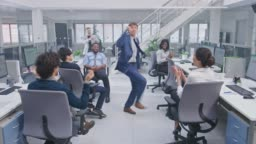 Young Happy Business Manager Wearing a Suit and Tie Dancing in the Office. Colleagues are Cheering. Diverse and Motivated Business People Work on Computers in Modern Open Office.