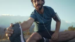 Young happy caucasian brunette man in his athletic clothes preparing to do some exercise outside and stretching his legs whilst sitting down