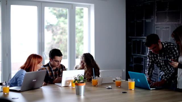 vidéos et rushes de jeunes collègues heureux travaillent ensemble sur un nouveau plan - graphisme