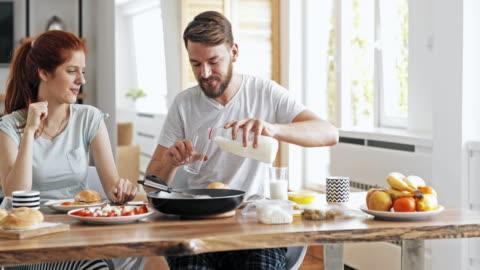 vídeos y material grabado en eventos de stock de joven pareja feliz de comunicación durante la hora del desayuno en el comedor. - desayuno