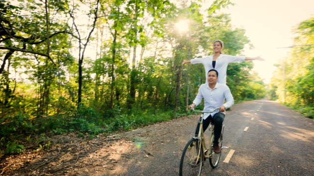 young happy couple enjoy riding a bicycle on natural road, love and relationship concept - southeast asian ethnicity stock videos & royalty-free footage