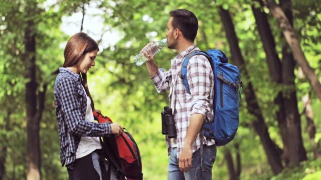 Junge Brautpaar mit einem gesunden Snack und Kommunikation beim Wandern in den Wald.