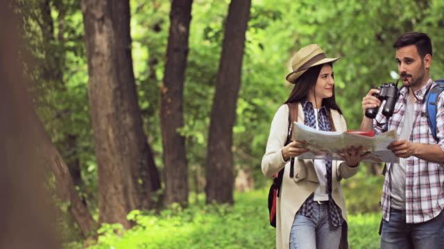 Jeune couple heureux randonnée dans la nature et à la recherche de la direction sur une carte.