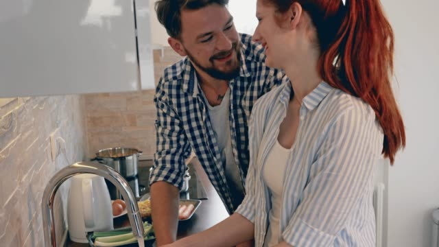 young happy couple in love preparing a meal in the kitchen. - happy meal stock videos & royalty-free footage