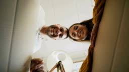 Young happy couple opening cardboard box and looking inside and closing it checking after relocation in new house