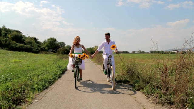 Young happy couple riding bicycles in countryside.