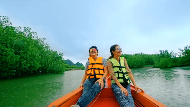 young happy couple sailing on a long tail thailand boat  through the mangrove forest in southern thailand - sailor stock videos & royalty-free footage