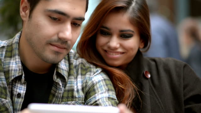 Young happy couple using tablet device