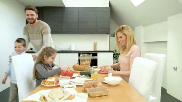 young happy family enjoying in a meal and communicating at dining table. - breakfast stock videos & royalty-free footage