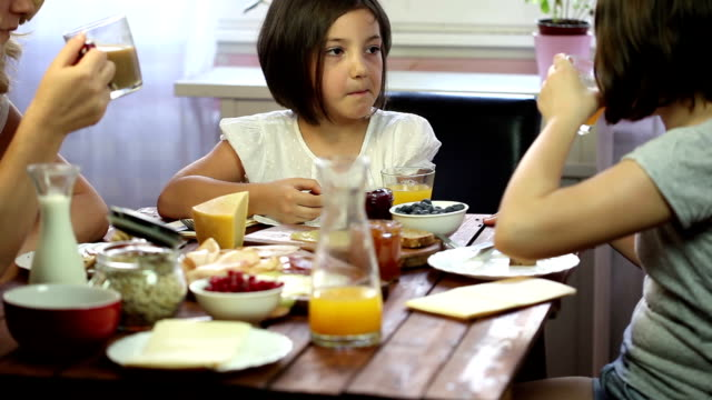 young happy family having breakfast - chewing stock videos & royalty-free footage