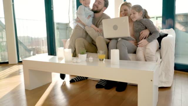 stockvideo's en b-roll-footage met jonge gelukkige familie met laptop in de woonkamer. - domestic room