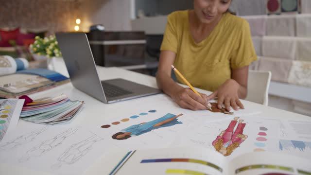 young happy fashion designer working on a new fashion collection at the studio using a laptop and sketches - fashion collection stock videos & royalty-free footage
