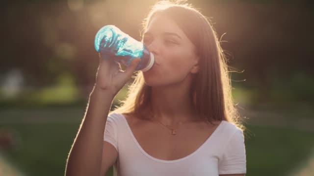 young happy girl drinks water from a bottle - portrait with water - hd video - video portrait stock videos & royalty-free footage