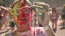 Young happy girl in colourful powder wears sunglasses and starts laughing on holi festival in daytime in summer, color concept