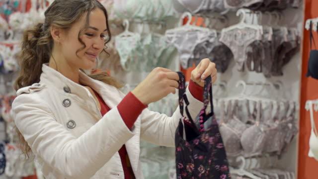 vídeos de stock, filmes e b-roll de jovem garota feliz mostrando underwear e pede orientação - peça íntima do vestuário