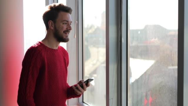 Young happy man text messaging on mobile phone by the window.