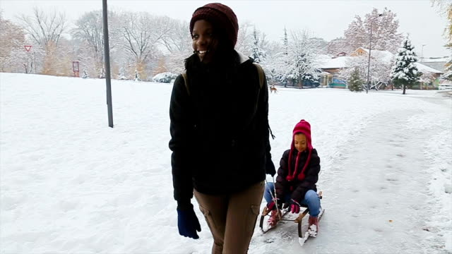 young happy mother and her little toddler daughter enjoying a sledge ride in a beautiful snowy winter park - tourism stock videos & royalty-free footage