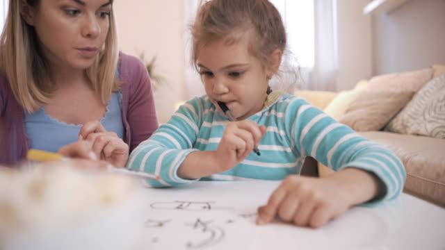 Jonge gelukkige moeder en haar kleine meisje plezier terwijl tekenen en thuis te communiceren.