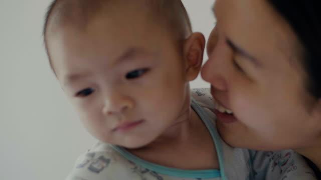 若い幸せな母保持と彼女の新生子供のキス - 託児施設点の映像素材/bロール