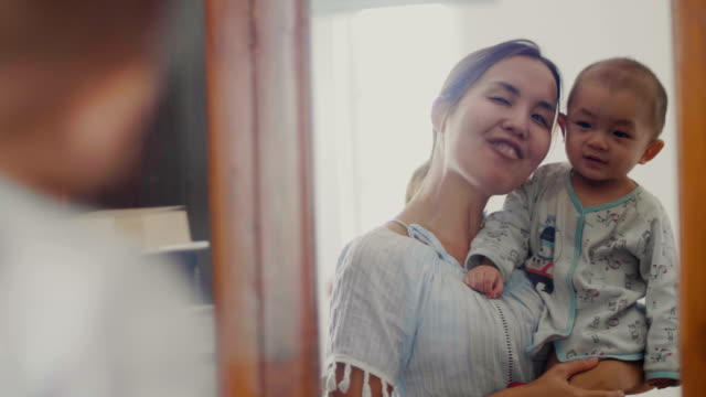 young happy mother holding her newborn child in front of mirror - in front of stock videos & royalty-free footage