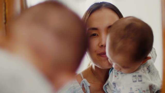 鏡の前で彼女の新生子供を保持している若い母 - 鏡点の映像素材/bロール