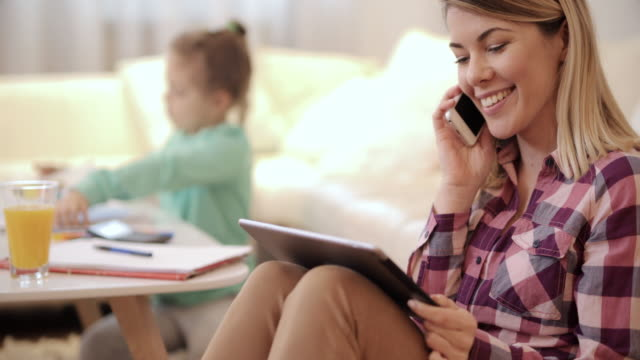 Young happy mother talking on mobile phone and using touchpad in the living room.