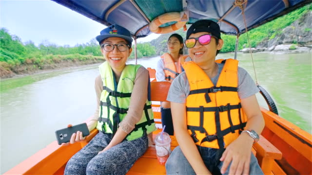 Young happy people sailing on a long tail thailand boat  through the mangrove forest in southern Thailand