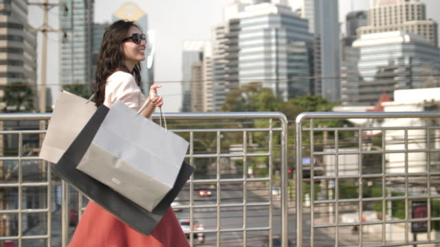 young happy pretty woman walks with shopping bags in the city - garment stock videos & royalty-free footage