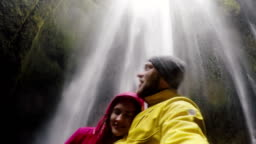 Young happy traveling couple taking a selfie on gopro camera. Man and woman near the Gljufrabui waterfall in Iceland