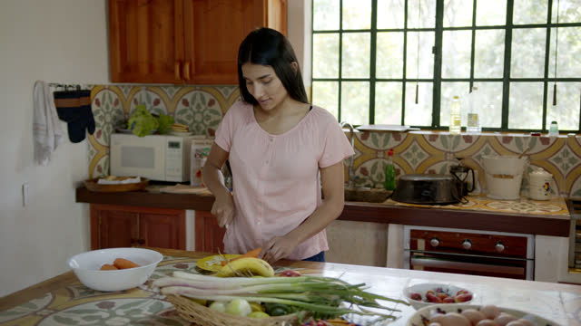 young happy woman at a countryside home chopping vegetables preparing a delicious healthy meal - colombia stock videos & royalty-free footage