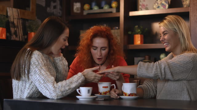 young happy woman showing engagement to her female friends in a cafe. - engagement ring stock videos and b-roll footage